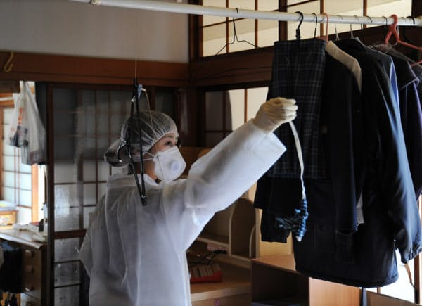 「これで見納め」。家族と過ごした「わが家」に一時帰宅した渡部郁子さん。家の中に干したままの高校時代の制服からリボンを取り出した(2011年11月26日、福島県大熊町)