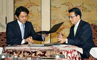 確認事項に署名する民主党の岡田代表(右)と維新の党の松野代表(26日午後、国会)=共同