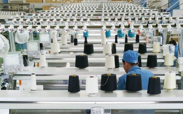 工場に並ぶ編み機の前で滑らかなフォルムを見せたニット服。「継ぎ目」のような変化も簡単に付けられる
