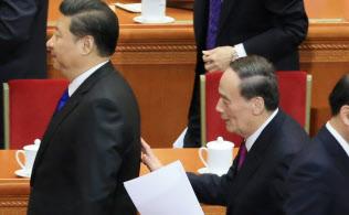 政治協商会議の開幕式を終えて習近平(左)に話しかける王岐山・政治局常務委員(北京の人民大会堂)=写真 小高顕
