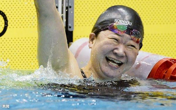 女子50メートル自由形でリオ・パラリンピックの派遣標準記録を切る好タイムを出し、ガッツポーズする成田=共同