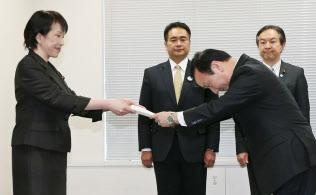 2015年末に高市総務相(左)からスマートフォンの料金や端末販売について要請書を受け取るNTTドコモの加藤薫社長