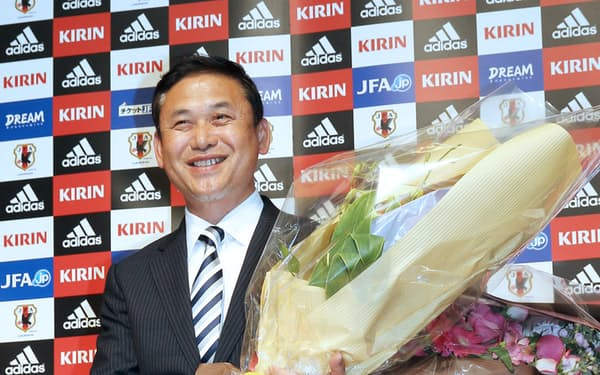 退任の記者会見の後、花束を手に笑顔を見せるサッカー日本女子代表の佐々木則夫監督(18日午後、東京都文京区)