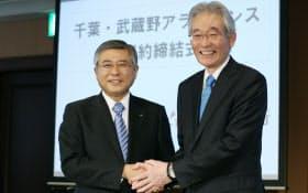 提携の署名を終え、握手する千葉銀行の佐久間頭取(左)と武蔵野銀行の加藤頭取(25日午後、東京都中央区)