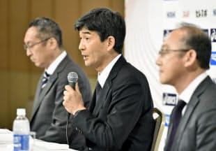 記者会見でリオ五輪のマラソン代表を発表する日本陸連の尾県貢専務理事(中央)ら=共同