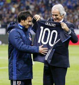 岡崎(左)は代表通算100試合に出場し、ハリルホジッチ監督から記念のユニホームを受け取った=共同