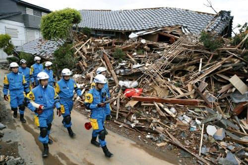 倒壊した住宅の状況を確認する警察官=17日、熊本県益城町