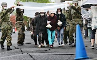 炊き出しのおにぎりを手にする女性ら。降り出した雨をよけるため自衛隊員がシートで覆った(21日午前、熊本県益城町)