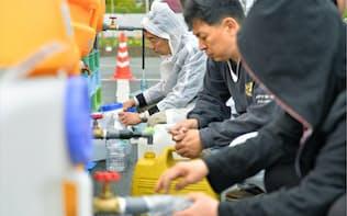 熊本県益城町の避難所で、雨の中給水をする人たち(21日午前7時45分ごろ)