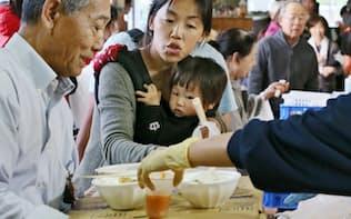 夕食時、避難所の配給をじっと見つめる子供(20日、熊本県益城町の広安小学校)