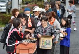 飲み物を受け取る被災者(22日午前、熊本県益城町の益城町総合体育館)
