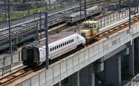 牽引車で車両基地に向かう脱線した九州新幹線の先頭車両(22日午後、熊本市西区)=写真 塩山賢