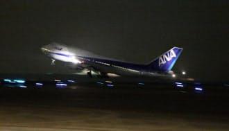 ANAが深夜貨物便による旅客輸送を始める背景には、565人もの乗客を乗せられるボーイング747型機の退役による輸送量の減少がある。写真は離日するANA最後の747(4月16日、羽田空港)