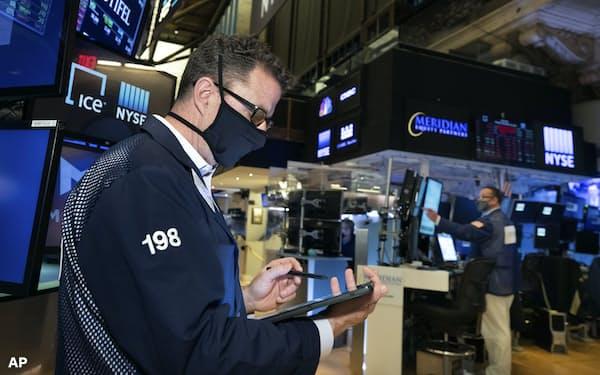 マスクをしてメモをするニューヨーク証券取引所内のトレーダー(AP)