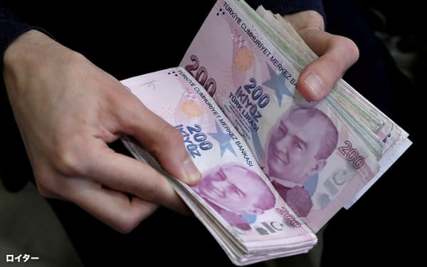 FILE PHOTO: A merchant counts Turkish lira banknotes at the Grand Bazaar in Istanbul, Turkey, March 29, 2019. REUTERS/Murad Sezer/File Photo