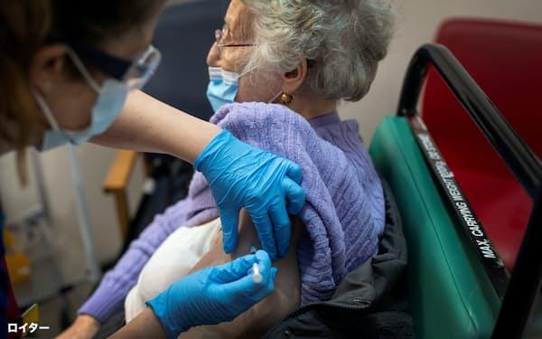 英国ロンドンでファイザーのコロナワクチンの接種を受ける女性(8日)=ロイター