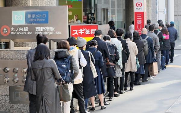 マスクを買い求めるため開店前のドラッグストアに並ぶ人たち(東京都新宿区)