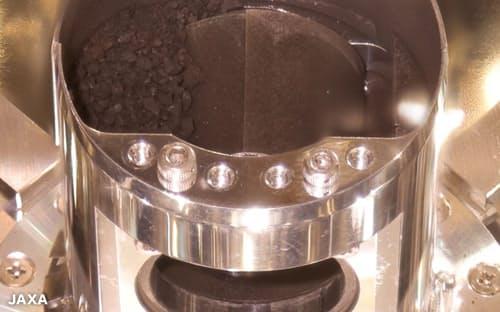 はやぶさ2カプセル内の容器、りゅうぐうの黒い大きな砂粒が左側に多数見える=JAXA提供