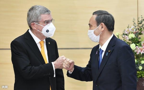 五輪開催による感染拡大リスクをきちんと伝える必要がある(11月16日、会談を前にIOCのバッハ会長(左)とグータッチを交わす菅首相)