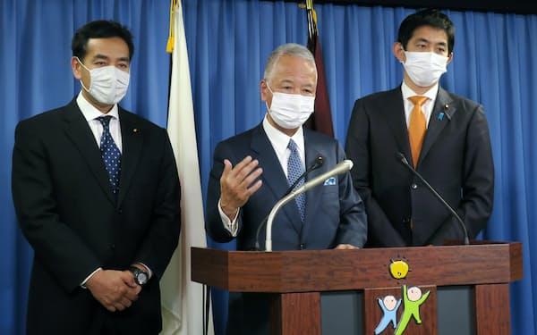 自民党の甘利明氏(中)は記者会見で提言を説明した(16日、党本部)