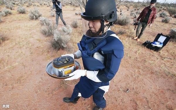 オーストラリアの砂漠で回収される「はやぶさ2」のカプセル=6日(JAXA提供)