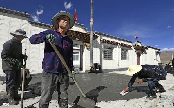 移住政策で建てられたチベット族の住宅前をコンクリートで舗装する作業員(10月16日、中国チベット自治区ラサ郊外)=共同
