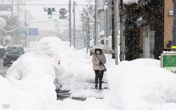 大雪の中、市街地を歩く女性=19日午後1時7分、新潟県南魚沼市
