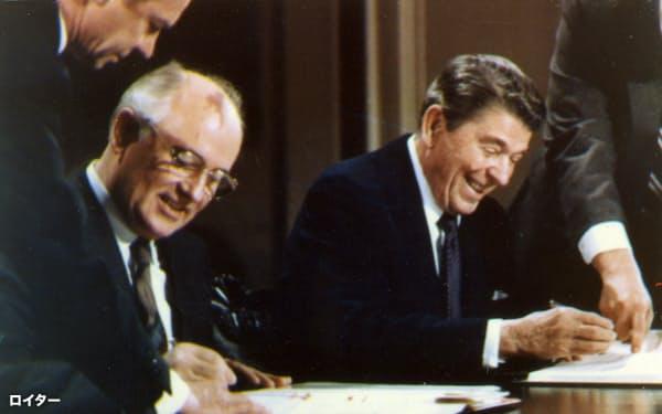 1987年12月、ホワイトハウスでINF廃棄条約に調印するレーガン米大統領(右)とゴルバチョフ・ソ連書記長=ロイター・共同