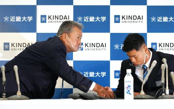 阪神から1位指名された近大の佐藤内野手(右)と握手する田中監督(2020年10月、大阪府東大阪市)=近大提供