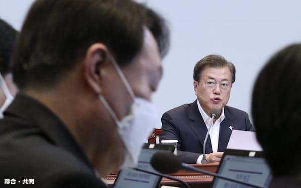 6月、韓国大統領府の会合に参加した文在寅大統領(奥)と尹錫悦・検察総長(ソウル市内)=聯合・共同