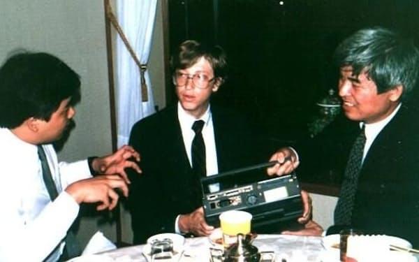 マイクロソフトのビル・ゲイツ氏にラップトップパソコンを説明する溝口氏(右)