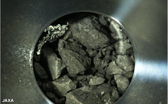 探査機「はやぶさ2」が小惑星への2回目の着陸で採取した小石などの試料(赤いバーは5ミリメートル)=JAXA提供