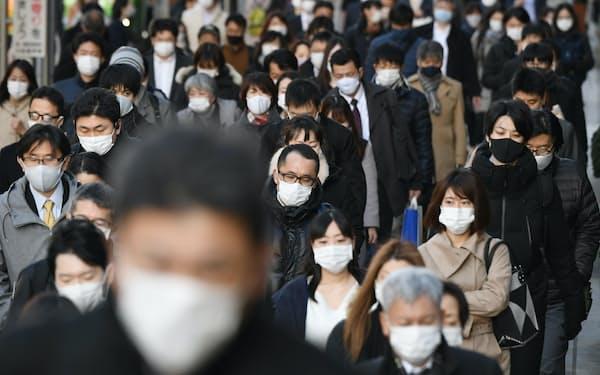マスク姿で通勤する人たち(18日午前、東京都中央区)