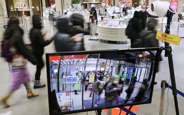 近鉄百貨店の初売りで検温システムの前を通過する来店客(2日、大阪市阿倍野区)