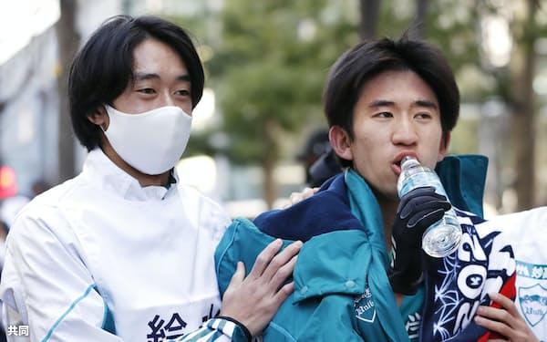 ゴールした青学大のアンカー・中倉(右)を支える神林主将=共同