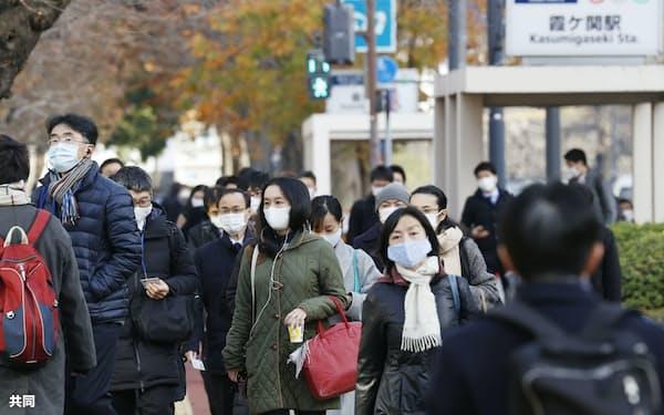 仕事始めを迎えた4日朝、マスク姿で職場に向かう人たち(東京・霞が関)=共同