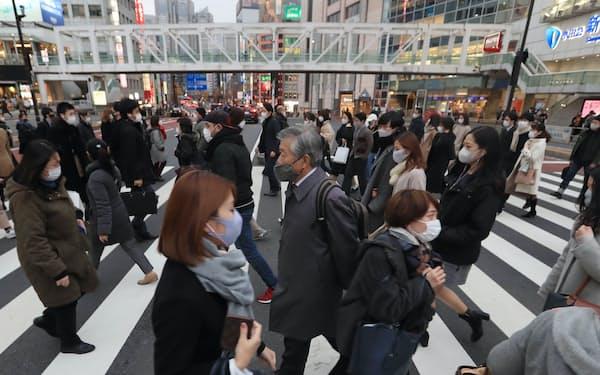 東京・新宿駅前をマスク姿で歩く人たち(6日午後)