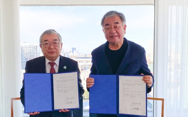 隈氏㊨とコンペ開催の確認書を交わす松岡町長(20年12月25日、東京都内)