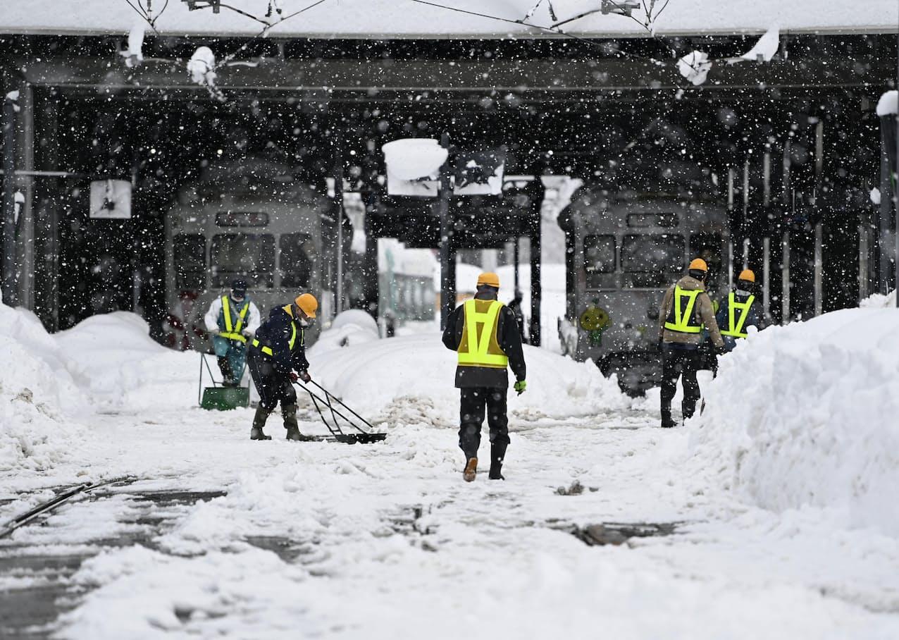 富山駅前で雪かきをする人たち(10日午前)=共同