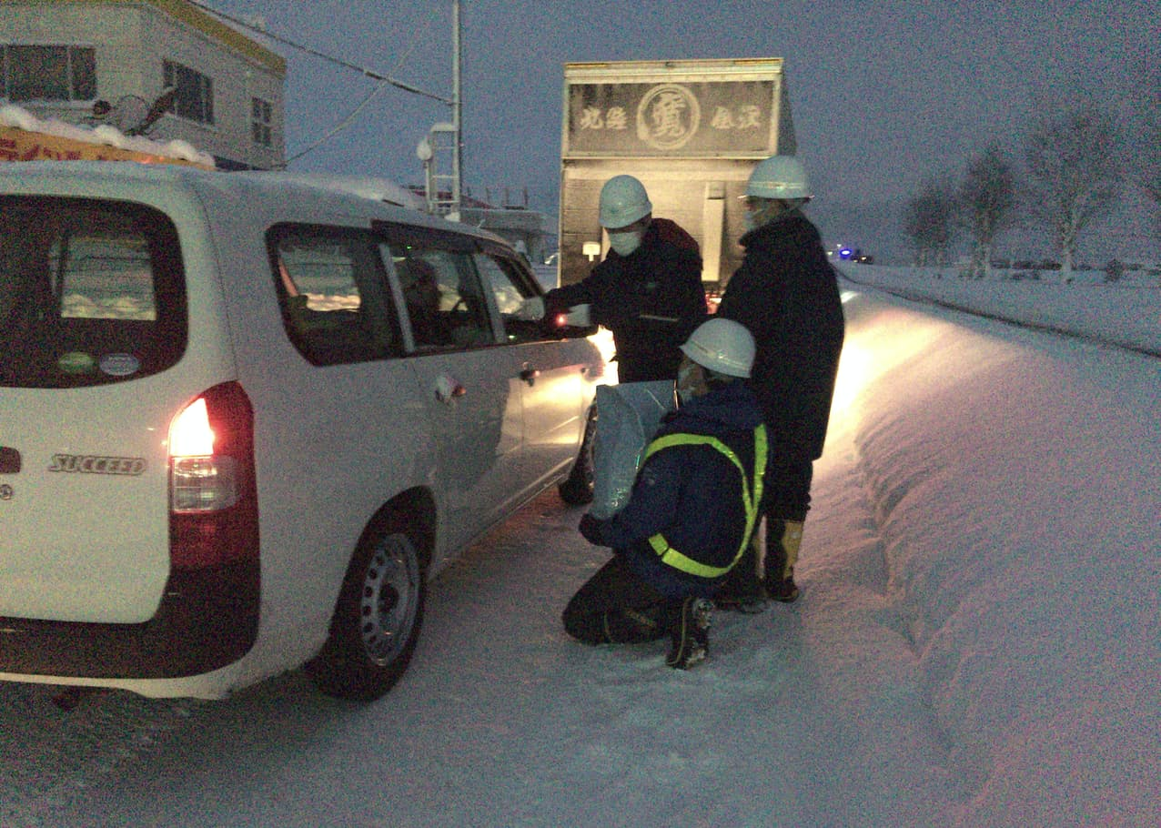 大雪の影響で渋滞する福井市の国道8号で、物資を配る国交省福井河川国道事務所の関係者(10日)=同事務所提供・共同