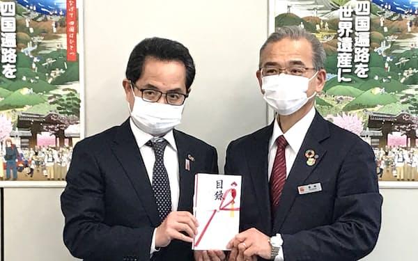 百十四銀の豊嶋正和取締役常務執行役員㊨が寄付金を贈呈した(12日、高松市)