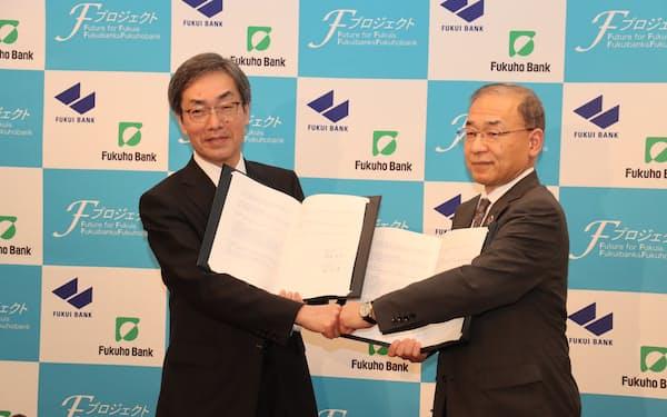 資本提携について発表する福井銀の林頭取(左)と福邦銀の渡辺頭取(14日、福井市)