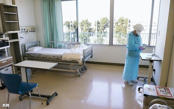 新型コロナウイルス患者の入室を前に、防護具を着用して病床の準備をする看護師=2020年12月22日、東京都三鷹市の杏林大病院