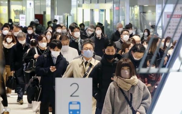 西鉄福岡駅でマスクを着けて通勤する人たち(14日午前、福岡市)=共同