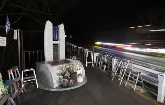 発生時刻となった現場付近の慰霊碑の脇を車が通過して行った(15日午前1時52分、長野県軽井沢町)=共同