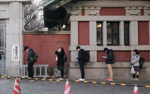 大学入学共通テストの会場前で間隔を空けて並ぶ受験生(16日午前、東京都文京区の東京大)