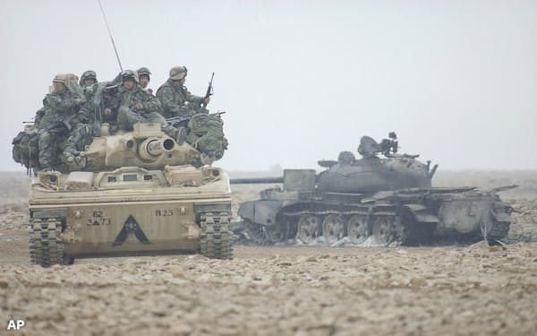 Member of the U.S. Army?s 82nd Airborne ride a Sheridan tank past a burned out Iraqi tank in Iraq?s desert on Monday, Feb. 26, 1991 in Iraq. (AP Photo/Tannen Maury)
