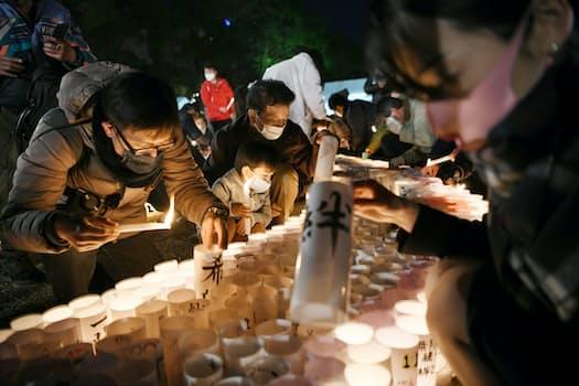 「がんばろう」の文字に並べられた灯籠に火をともす人たち(16日午後、神戸市中央区の東遊園地)