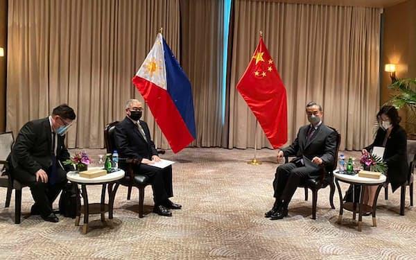 会談する中国の王毅外相(中央右)とフィリピンのロクシン外相(中央左)=16日、マニラ