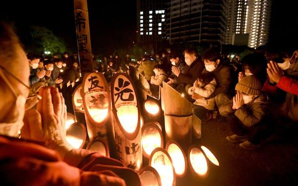 阪神大震災の発生時刻に合わせて黙とうする人たち(17日午前5時46分、神戸市中央区の東遊園地)